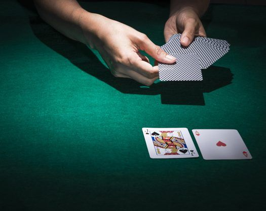 hand-holding-poker-cards-casino-table_23-2147881603-e1558336080396.jpg